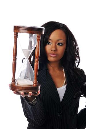 woman clock: Empresaria de j�venes afroamericanos sosteniendo un reloj de arena aislado en blanco