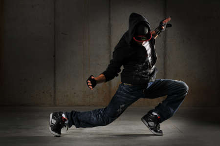 rapping: Hip hop dancer performing against a grunge wall Stock Photo