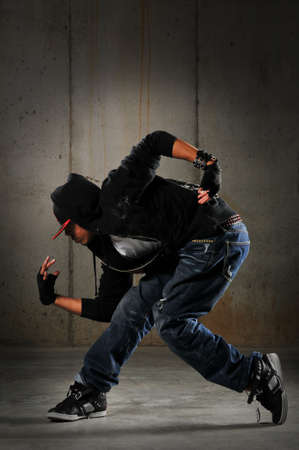Hip hop dancer performing against a grunge wall photo