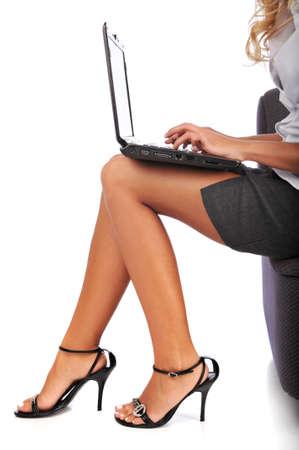pies sexis: Empresaria utilizando un ordenador port�til aislado contra un fondo blanco