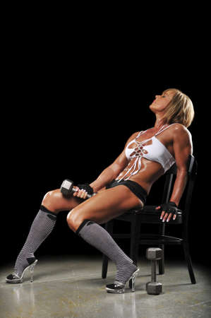tired: Muscular mature woman resting afte a workout on a black background