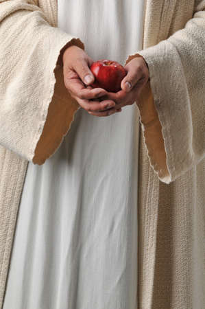Jesus's hands holding an apple as a symbol of producing fruit Stock Photo - 8037952