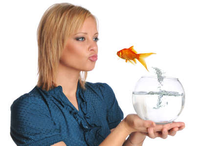 Young woman kissing a jumping goldfish isolated on a white background photo