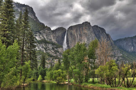 Yosemite view from the river with water fall an cloudy sky photo