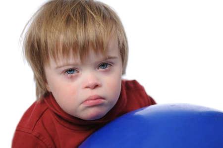 白い背景で隔離のボールで遊ぶダウン症候群を持つ少年