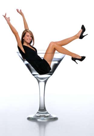 copa de martini: Mujer joven en un vaso de martini celebrando ans aislado en un fondo neutro