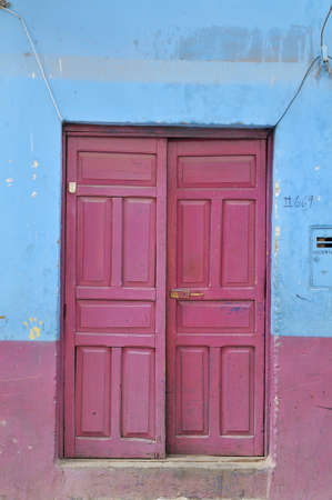 Old grungy door in red tones and  textured walls photo