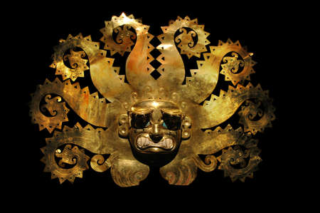 Peruvian ancient mask made out of gold and zaphire isolated on a black background