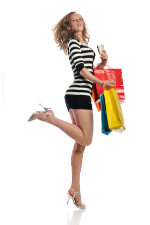 Woman holding credit cards and shopping bags jumping against a white background