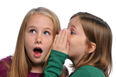 whispering: Two girls telling a secret and expressing surprise isolated on white Stock Photo