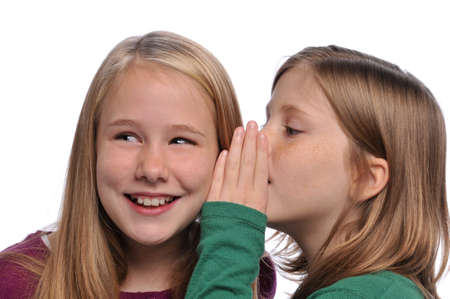 Little girls sharing a secret isolated on a white background photo