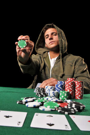 Young man playing poker and holding some chips against a black background