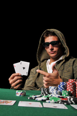 card player: Young man playing poker and holding a couple of aces against a black background