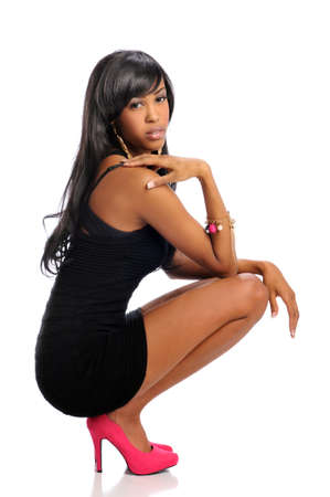 legs heels: African American woman posing wearing a black dress and high heels Stock Photo