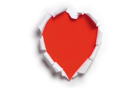 Ripped paper in the shape of a heart against a red background Stock Photo