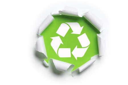 reciclaje papel: papel rasgado de blanco con el logo de reciclaje contra un fondo verde Foto de archivo