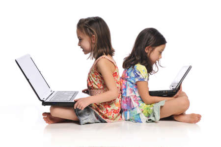 Two little girls with laptop computers isolated on a white background Banco de Imagens