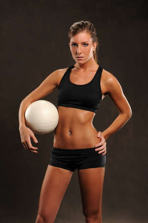 beach volleyball: Young Volleyball player woman posing with a ball isolated on a dark background