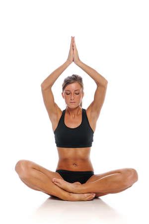 Jonge vrouw tijdens een sessie van de yoga geïsoleerd op een witte achtergrond