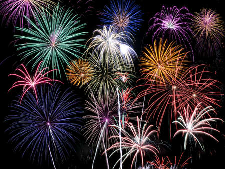Fireworks of multiple colors bursting against a black background photo