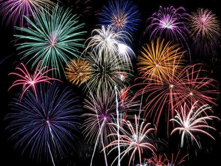 Fireworks of multiple colors bursting against a black background photo