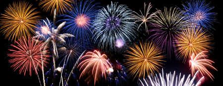 Fireworks of multiple colors bursting against a black background
