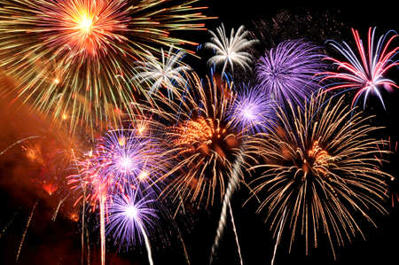 Fireworks of various colors bursting against a black background