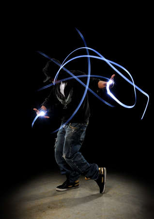Hip Hop Dancer performing showing traces of lighs against a dark background Stock Photo