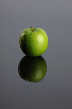 Green apple with reflection on a gray background Stock Photo - 9132933