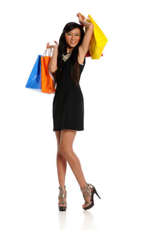 shopper: Young Oriental Woman with shopping bags isolated on a white background