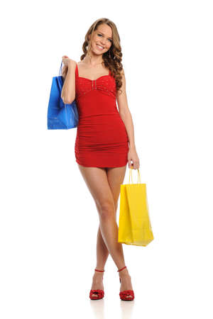 carying: Young Woman wearing a red dress and carying shopping bags isolated on a white background