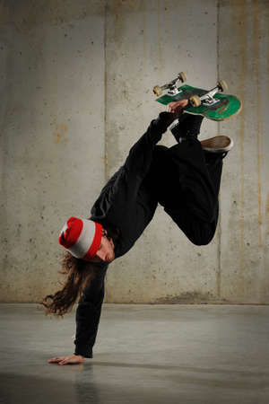 Skateboarder performing tricks with grungy wall as background photo