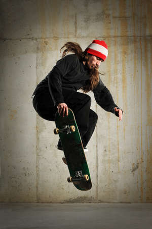 Skateboarder performing tricks with grungy wall as background