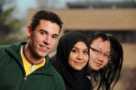 Diverse Group of Students smiling with college campus on the background Stock Photo
