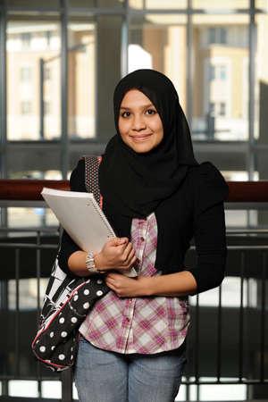 젊은 아랍 학생 카피 북을 들고 그녀의 전통적인 베일을 착용