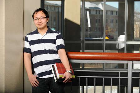 背景として大学のキャンパス内に本を抱えている若い東洋男 写真素材