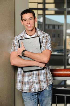 背景として大学建物と彼のラップトップ コンピューターを持って若い男