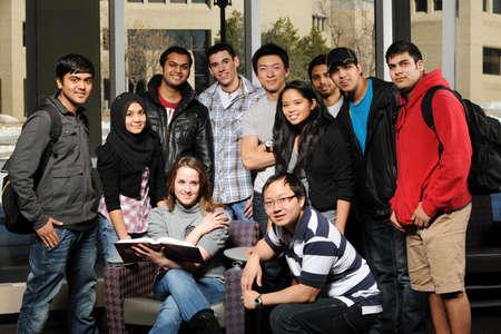 背景の建物大学キャンパスにおける学生の多様なグループ