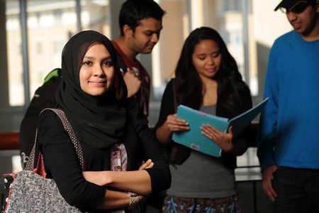 th�?¨: Estudiante joven �rabe sosteniendo libros en campus de la universidad con un grupo diverso en el fondo del tha