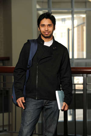 college building: Young Eastern student holding a book inside a College building Stock Photo