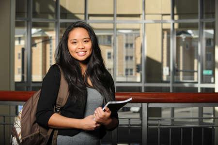 若いオリエンタル女性学生、大学のキャンパス内コピーブックを保持