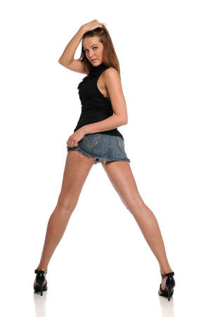 Young woman wearing a mini skirt and heels isolated on a white background