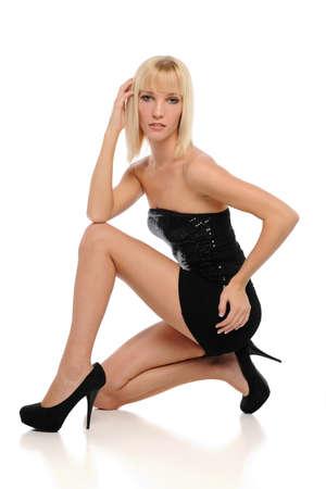 mini falda: Joven rubia que llevaba un vestido negro aislado en un fondo blanco