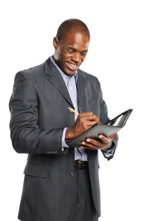 black businessman: Young smiling black businessman taking notes isolated on a white background Stock Photo