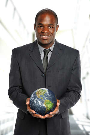 african business man: Young African American Businessman holding the earth inside an office building Stock Photo