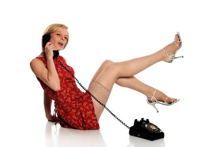 Pinup Woman wearing a red dress and holding a vintage telephone isolated on a white background photo