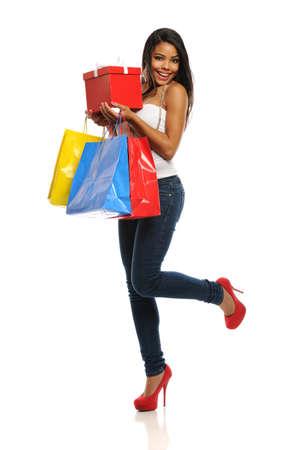Joven mujer afroamericana con bolsas de la compra aislados en un fondo blanco