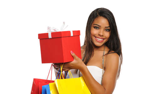 shopper: Young African American woman holdring a present and shopping bags isolated on white backgroung Stock Photo