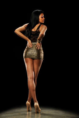 minifalda: Joven mujer afroamericana, vistiendo zapatos de tacón alto y una mini falda sobre un fondo oscuro