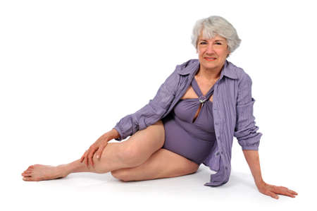 75s: Attractive Senior Citizen Lady wearing a swimming suit on a white background